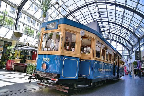 blue and yellow tram in shopping area