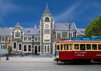 Stone historic building, arts centre with red and yellow tram infront