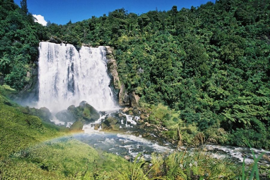 Large falls over roacks surrounded by forest and a little rainbow in the foreground