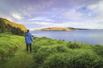Lady in blue jacket walking on a lawn looking over Hokianga Harbour
