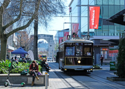 City Tour tram in Christchurch going through city, bridge of remembrance in background